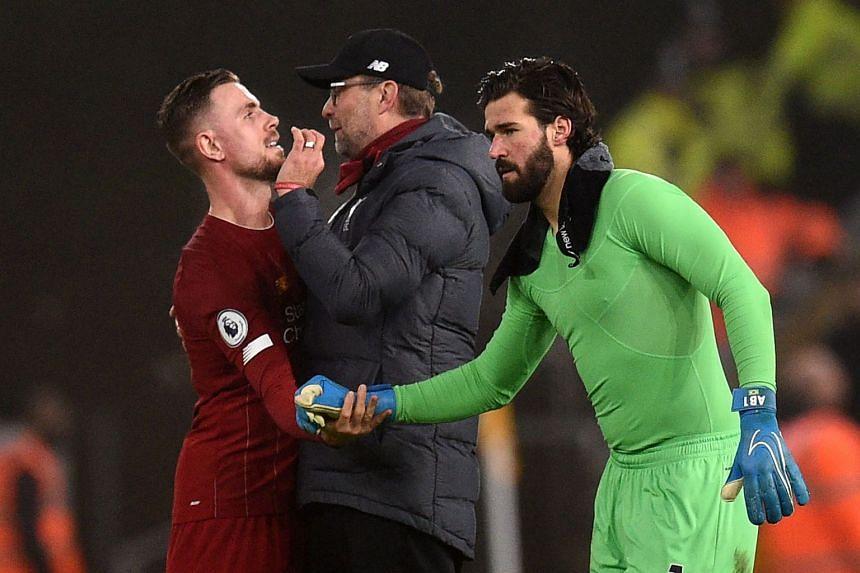 Liverpool's Jordan Henderson (left), manager Jurgen Klopp (centre) and goalkeeper Alisson Becker celebrate after a match.