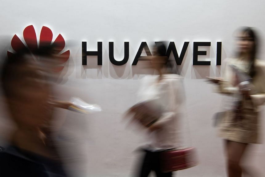 People walk past a Huawei logo during the Consumer Electronics Expo in Beijing in August 2019.