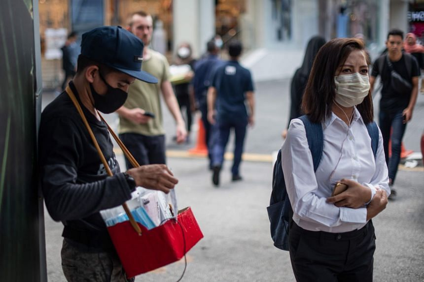 A man (left) sells protective face masks in Kuala Lumpur on Feb 13, 2020.