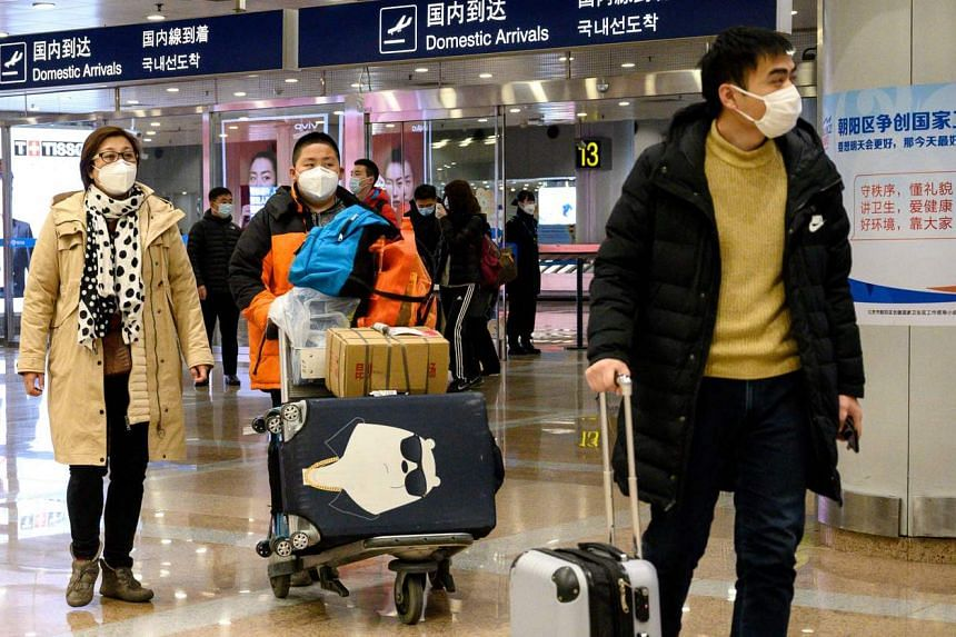 Passengers, wearing face masks, walk at the arrival area of the Beijing Capital International airport, on Jan 31, 2020.