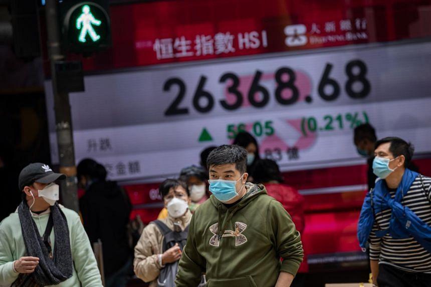 Pedestrians walk past an electronic billboard showing the Hang Seng Index figures in Hong Kong, on Feb 3, 2020.