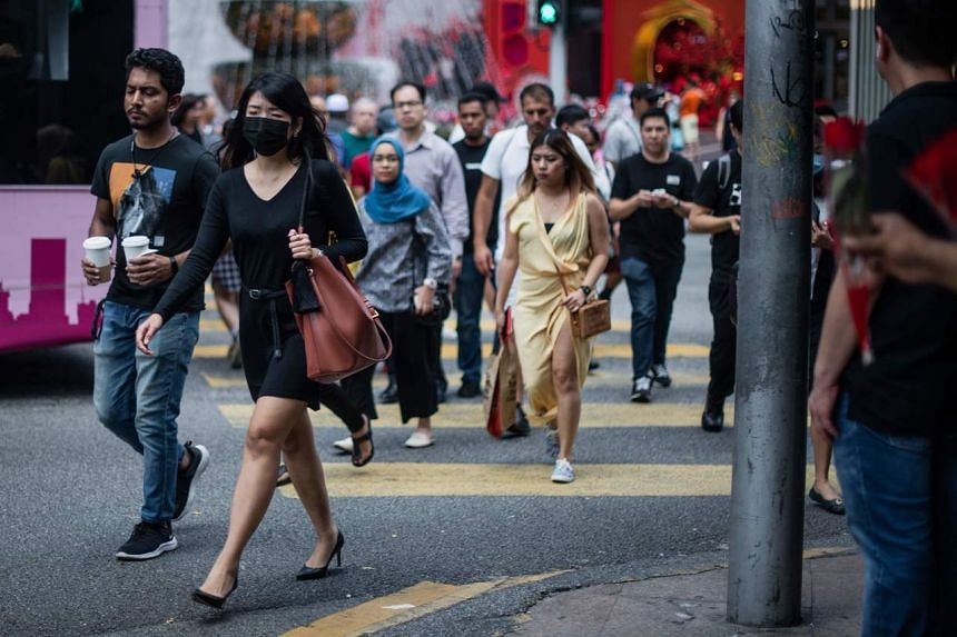 A woman with a face mask walking among pedestrians in Kuala Lumpur, on Feb 13, 2020.