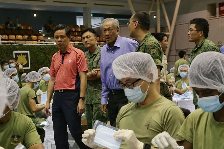 Trade and Industry Minister Chan Chun Sing (left), Defence Minister Ng Eng Hen observing the packing of masks by SAF servicemen at Safti Military Institute, on Jan 31, 2020.