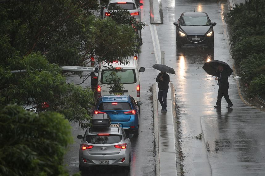 Pedestrians brave strong wind and rain in Sydney, New South Wales, Australia, on Feb 9, 2020.