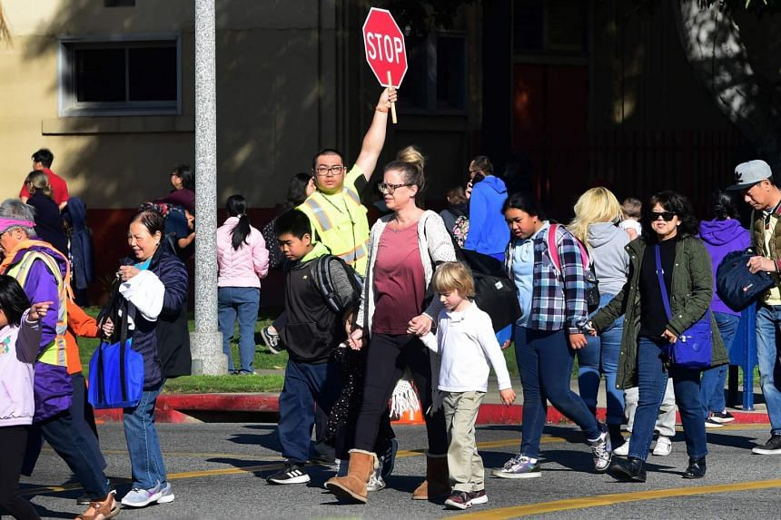 In a photo taken on Feb 4, 2020, an Alhambra Unified School District crossing guard stops traffic for parents picking up their children from Ramona Elementary School.