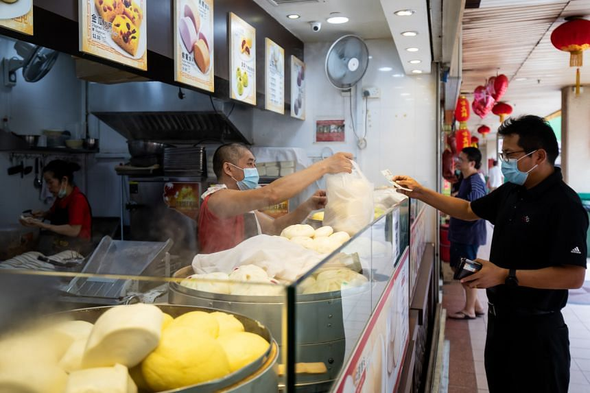 A customer pays a vendor at a food stall in the Chinatown area of Singapore, on Feb 10, 2020.