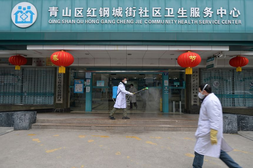 A doctor disinfects the entrance of a community health service centre in the Qingshan district of Wuhan, Hubei, on Feb 2, 2020.