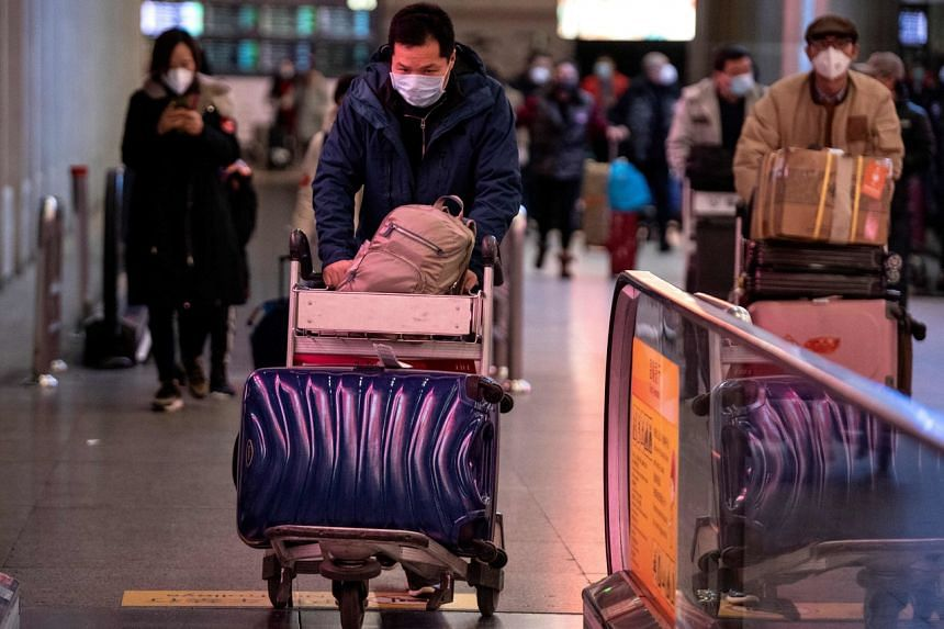 A passenger wearing a protective face mask pushes a trolley as he arrives at the Beijing Capital International Airport on Feb 2, 2020.
