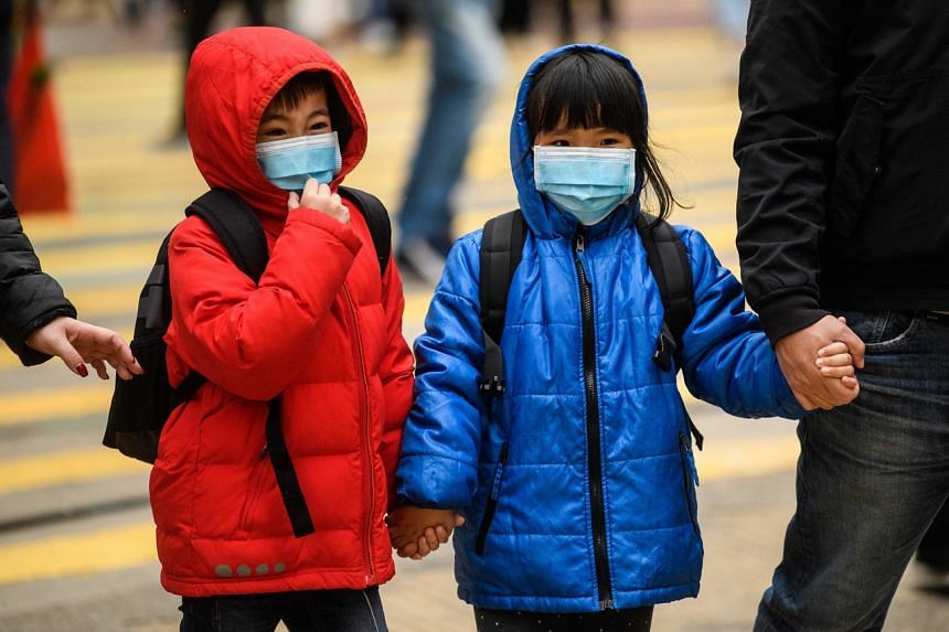 Children wearing face masks crossing a road in Hong Kong on Jan 27, 2020. Hong Kong students have not gone to school since the scheduled Chinese New Year break began in late January.