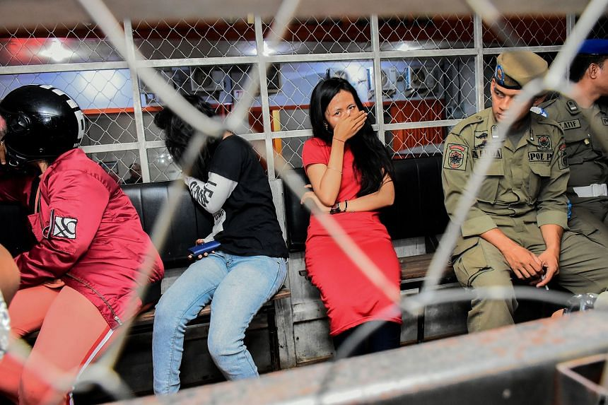 Women detained during a raid at a hotel in Makassar, Indonesia, where they were caught in the rooms with men who are not their husbands, on Feb 13, 2020.