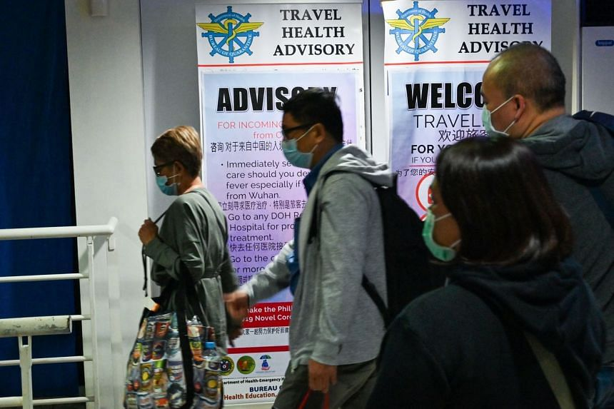 Travellers wearing protective face masks walk past a travel health advisory sign upon arrival at the international airport in Manila on Feb 5, 2020.