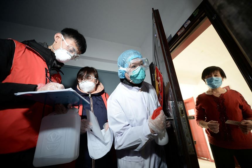 Medical workers visit a woman at her home in Tianjin, China, as they inspect residents following the coronavirus outbreak on Feb 12, 2020.