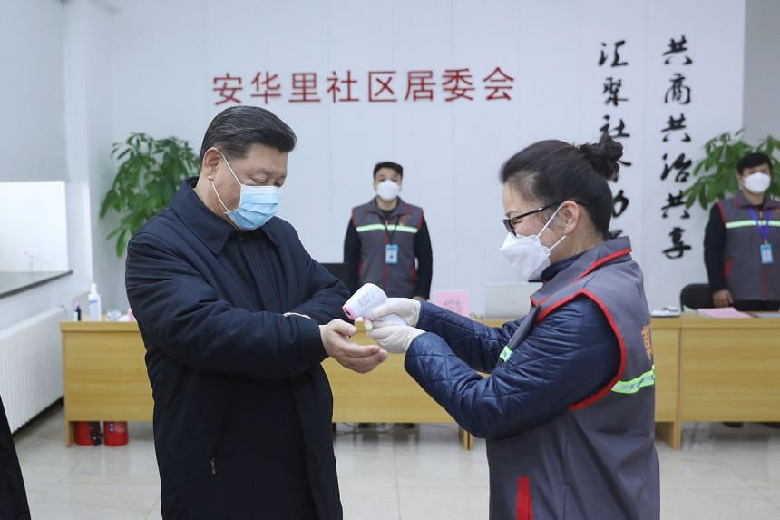 Chinese President Xi Jinping is seen wearing a mask as a health official checks his temperature during an inspection of virus control measures in Beijing on Feb 10, 2020.