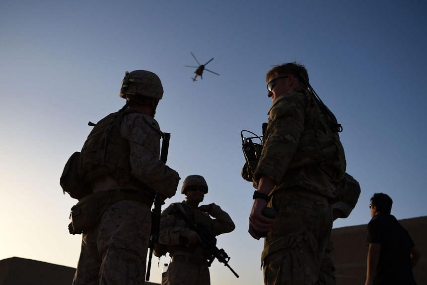 In a file photo taken on August 27, 2017, US Marines and Afghan Commandos stand together as a helicopter flies past during a combat training exercise in Lashkar Gah.