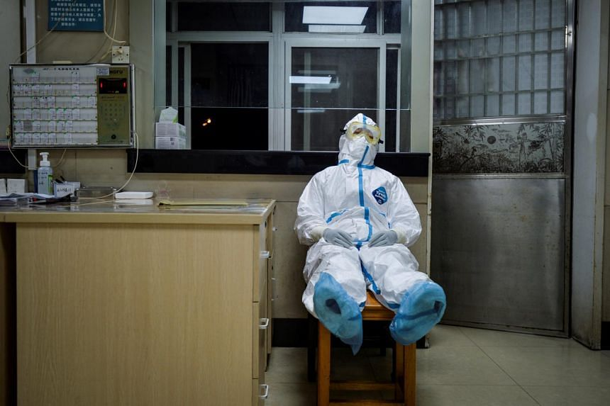 A medical worker in protective suit taking a break on Feb 9, 2020, during her night shift at a community health service centre, which has an isolation section to receive coronavirus patients with mild symptoms, in the Qingshan district of Wuhan, Chin