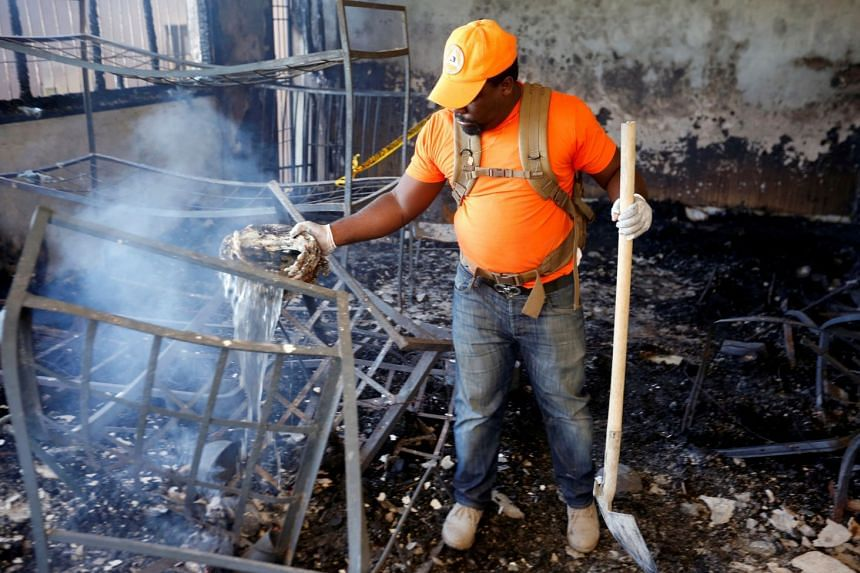 A civil protection worker pours water over burning debris inside a bedroom at the orphanage.