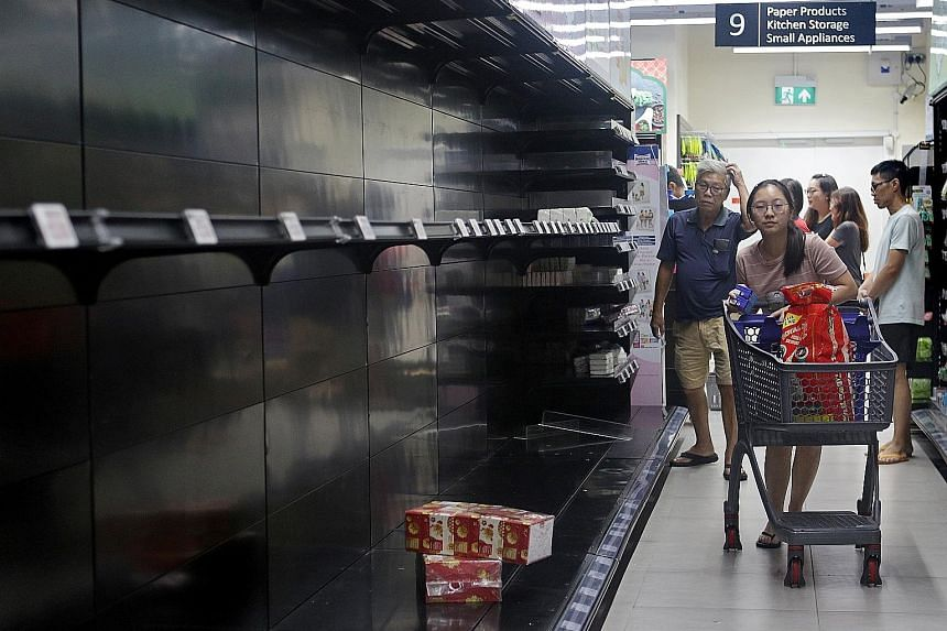 Scenes of panic buying were seen at supermarkets across the island last weekend. A shopper at a FairPrice Finest outlet in Paya Lebar (above) walking past empty shelves last Saturday.