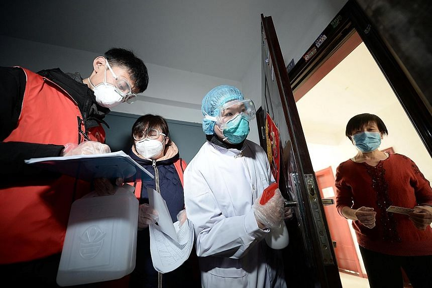 Community workers and medical staff visiting a woman at her home in Tianjin on Wednesday as they conducted door-to-door searches to inspect residents during the current coronavirus outbreak.