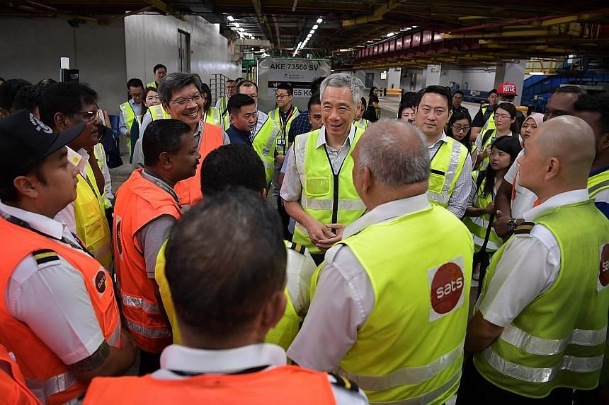 Prime Minister Lee Hsien Loong and Senior Minister of State for Transport and Health Lam Pin Min visiting baggage handling workers at Changi Airport Terminal 3 yesterday. PM Lee said the economic impact of the virus outbreak, particularly in the next
