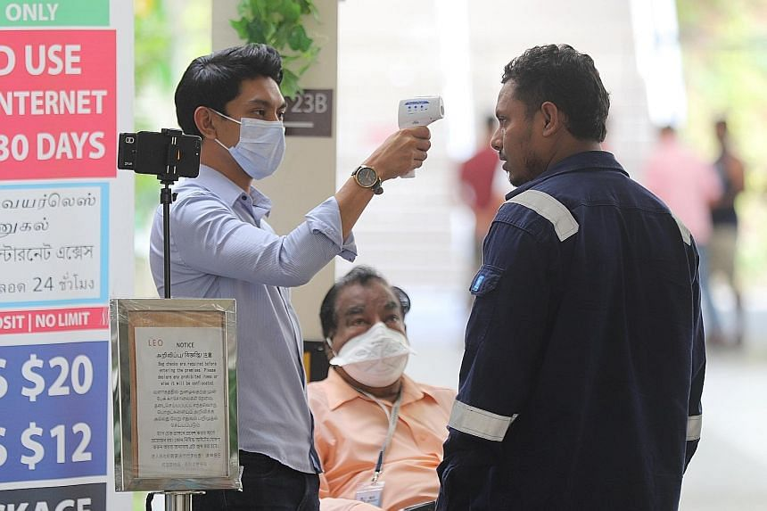Far left: The Avenue South Residence project is facing construction delays because of a disruption in the deliveries of supplies from China, where factory openings are deferred. Left: A man getting his temperature taken at The Leo dormitory in Kaki B