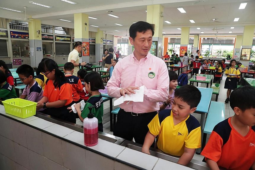 Education Minister Ong Ye Kung washing his hands together with pupils at First Toa Payoh Primary School yesterday. He was there to launch a campaign to rally pupils against the coronavirus, ahead of Total Defence Day today. The campaign's objectives