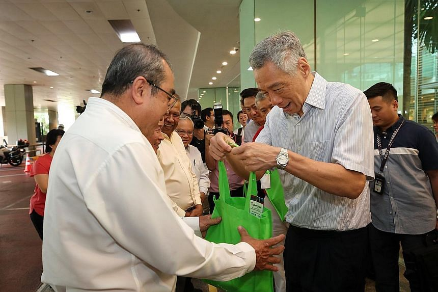 Prime Minister Lee Hsien Loong handing out care packages to taxi drivers at Changi Airport yesterday to thank them for continuing to ferry passengers amid the coronavirus outbreak. PHOTO: LEE HSIEN LOONG/FACEBOOK