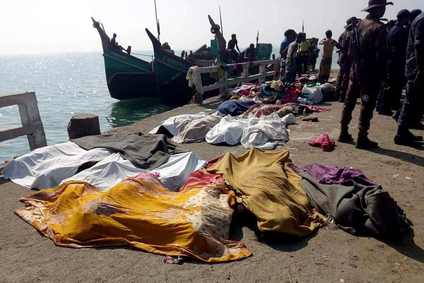 Bodies covered in sheets lying on a quay after a trawler capsized off the Bay of Bengal, in Teknaf, Bangladesh, on Feb 11, 2020.