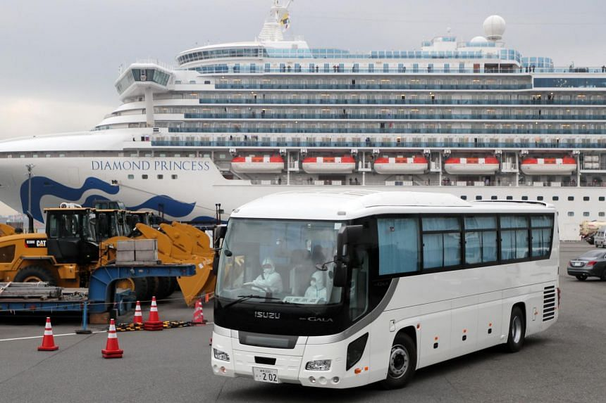 A bus with closed curtains leaving the Daikoku Pier Cruise Terminal, where the Diamond Princess cruise ship is docked, in Yokohama, Japan, on Feb 14, 2020.
