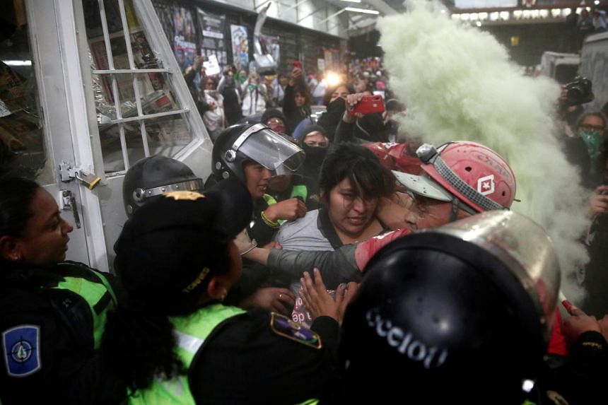 Protesters and security forces scuffle amid a cloud of tear gas during a protest against gender-based violence in downtown Mexico City on Feb 14, 2020.