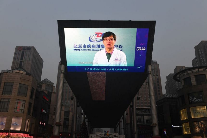 A news item about the Covid-19 coronavirus plays on a giant screen outside a shopping mall in Beijing on Feb 12, 2020.