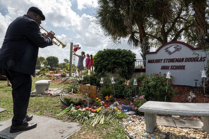 Canadian musician Laporte Massillon playing the trumpet in honour of the shooting victims in the makeshift memorial in front of the Marjory Stoneman Douglas High School in Parkland, Florida, on Feb 14, 2020.