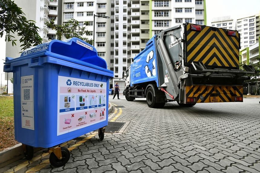 A recycling bin beside a Blue Recycling Truck at 524A Tampines Central 7 on Aug 29, 2019.