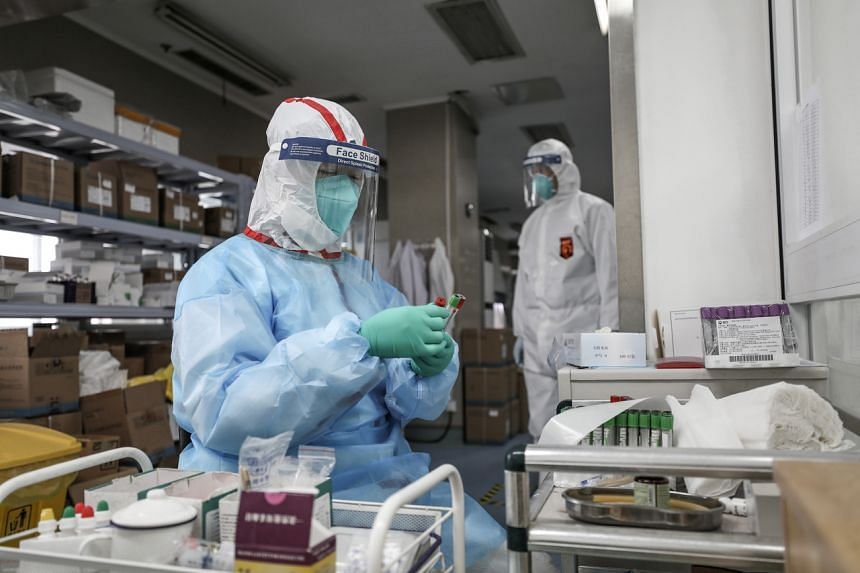 A medical worker in protective suit prepares for an RNA test at Jinyintan hospital in Wuhan, China, on Feb 13, 2020.