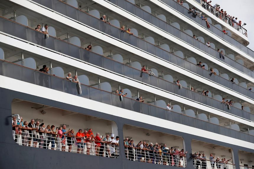 Passengers waving their towels as they prepare to leave MS Westerdam, which has docked in Sihanoukville, Cambodia on Feb 14, 2020.