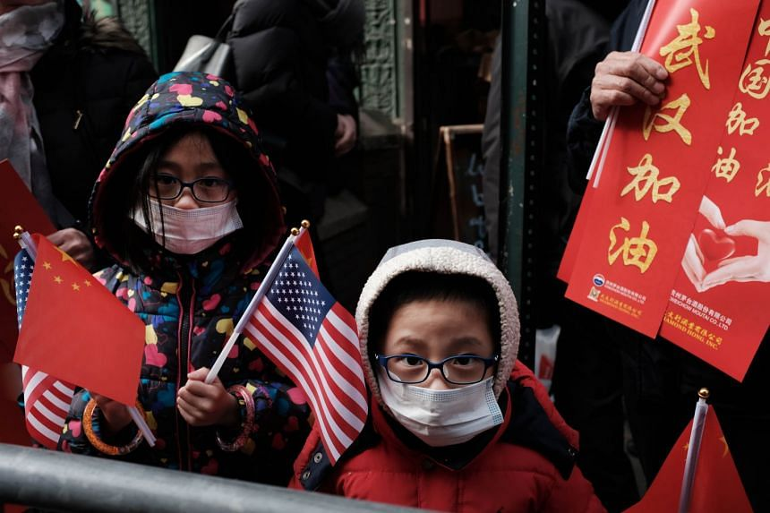 Children wearing surgical masks watch the annual Chinese New Year Parade in Manhattan's Chinatown on Feb 9, 2020 in New York City.