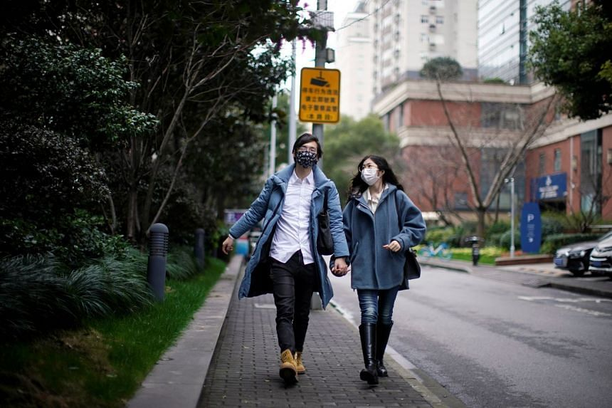 A couple with masks walking on a street on Valentine's Day, Feb 14, 2020, in Shanghai.