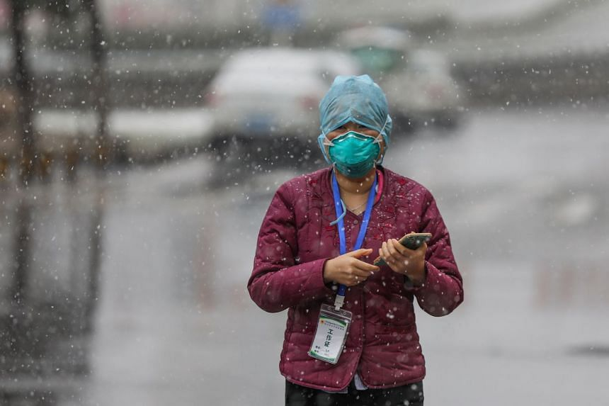 A government worker waits for patients to arrive outside a tumour hospital which was just designated to take in critical Covid-19 patients in Wuhan, in central China's Hubei province, on Feb 15, 2020.