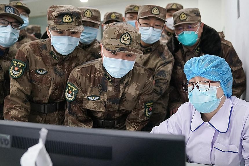 A doctor being disinfected by his colleague earlier this month in a quarantine zone in Wuhan, the city in China's central Hubei province that is the epicentre of the coronavirus outbreak. A People's Liberation Army medical team starting work on Jan 2
