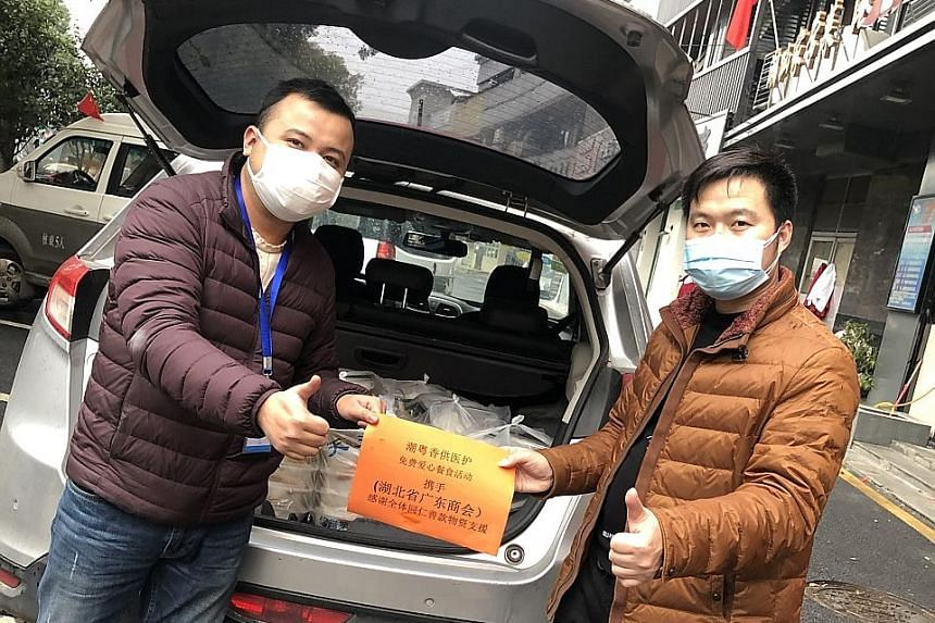 Restaurant owner Fang Zhongqin (right) with the lunch boxes his kitchen has been preparing for medical workers that are delivered to hospitals in Wuhan every day since the start of the outbreak. Mr Fang at his eatery, Chao Yue Xiang Seafood Restauran