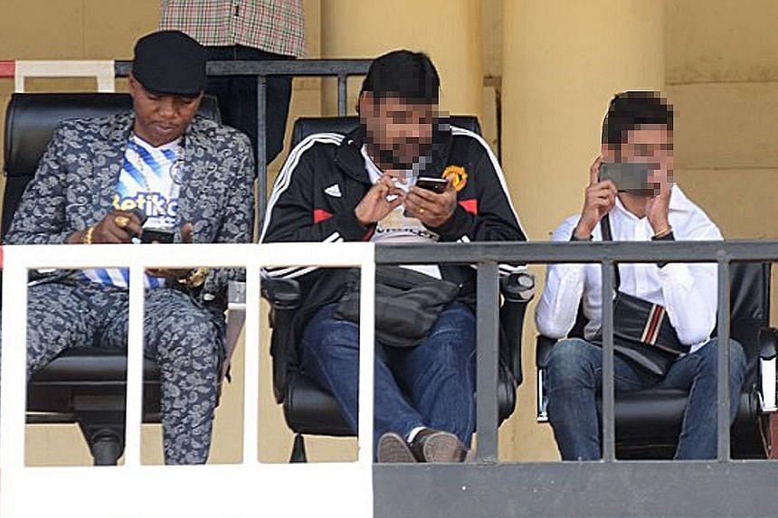 Above: Mr Kalekwa (far left) and two Singaporeans watching his club play on Aug 30 last year. Left: Mr Kalekwa with a Singaporean who inked a deal on behalf of a Hong Kong-based firm on Aug 2 last year. Sofapaka FC chairman Elly Kalekwa (third from l