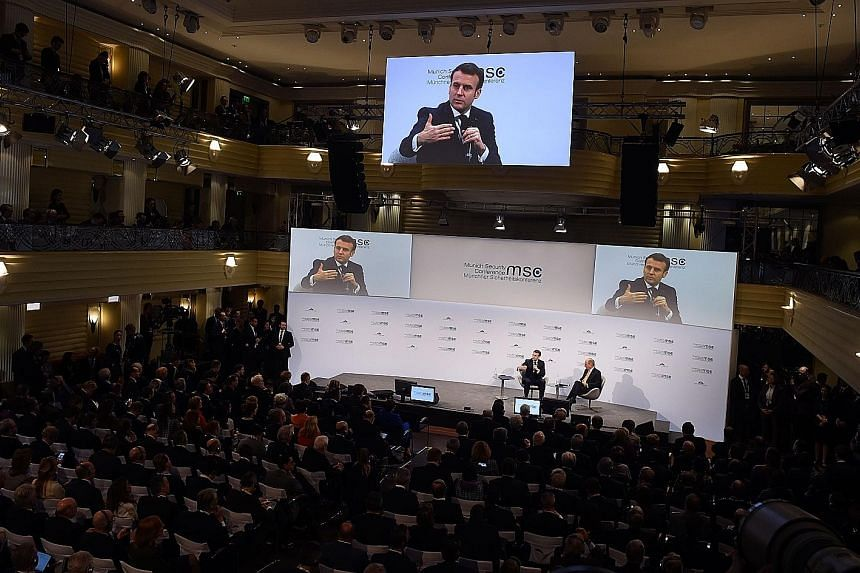 France's President Emmanuel Macron (left) sharing the podium with the chairman of the Munich Security Conference Wolfgang Ischinger during the 56th Munich Security Conference in Germany yesterday.