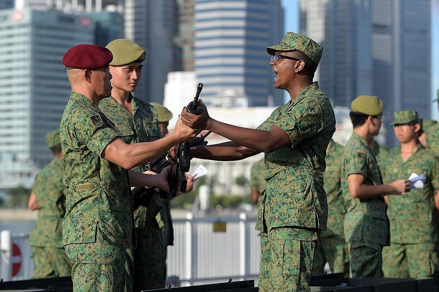 Basic Military Training Centre recruits receiving their SAR-21 rifles from their officers during the Total Defence Day Commemoration Event yesterday at The Float @ Marina Bay.