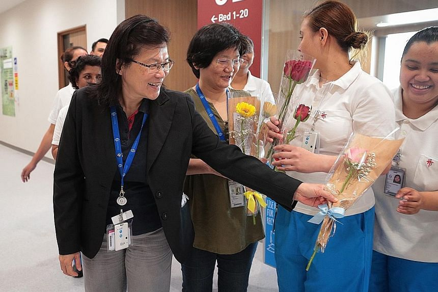 NCID executive director Leo Yee Sin with flowers for her staff from the public. With her are (from left) director of nursing Margaret Soon and nurses Ma. Olivia Valencia Valiente and Nurul Hazirah Subari.
