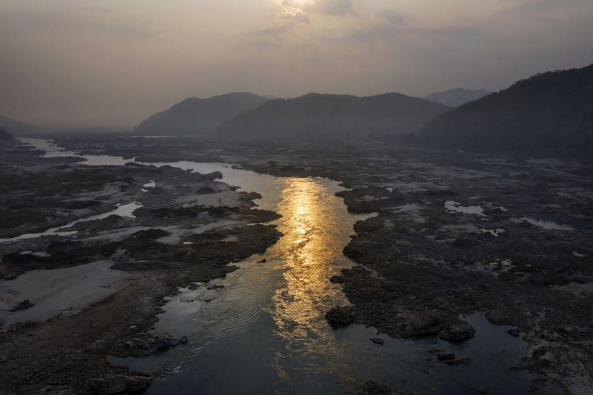 A narrowed Mekong River flows through the centre of its partially dried out riverbed near Sangkhom, Thailand, on Jan 25, 2020.