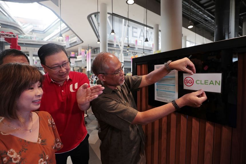 Environment and Water Resources Minister Masagos Zulkifli puts up the new decal with Senior Minister of State Amy Khor (left) and chief executive of food services business at FairPrice Group Alden Tan during the launch of the SG Clean campaign at Our