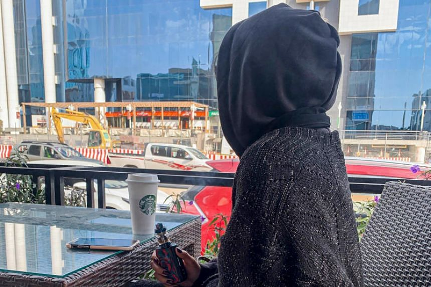 Rima, a 27-year-old Saudi woman, holds her electronic cigarette as she vapes at a coffee shop in downtown Riyadh, on Jan 26, 2020.
