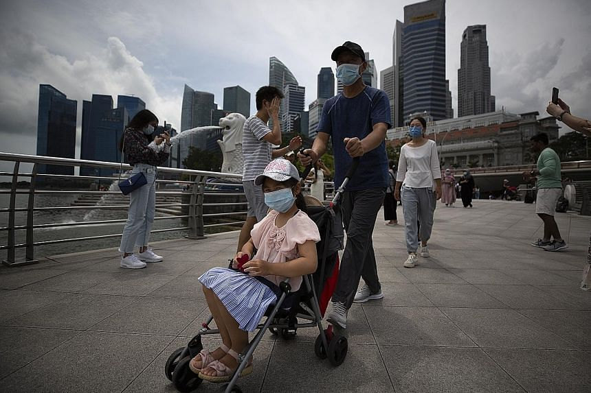 Tourists wearing face masks at Merlion Park. The financial impact on economies and companies from the coronavirus outbreak is expected to be worse than the 2003 severe acute respiratory syndrome epidemic. This is due in part to China's role in the gl