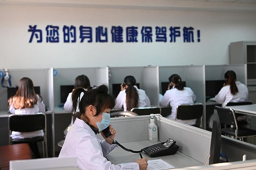 A hotline operator for a free counselling service in Shenyang, China, answers a phone call while wearing a face mask as the country is hit by an outbreak of the coronavirus.