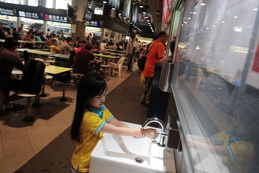 "(Far left) The ""SG Clean"" quality mark at a hawker stall in Our Tampines Hub. (Left) Chua Yu Xuan, seven, washing her hands at the same hawker centre yesterday. Posters have been put up at hawker centres to encourage customers to practise good person"