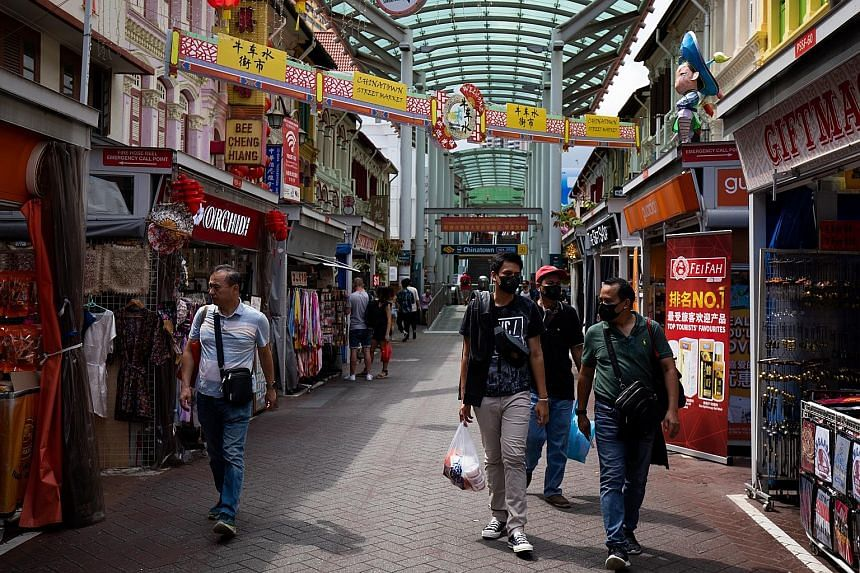 Shoppers wearing protective masks in a shopping street in Singapore's Chinatown area last week. A decline in overall retail sales last year suggests the spread of the coronavirus can dampen consumer sentiment, said Colliers International, but rents a